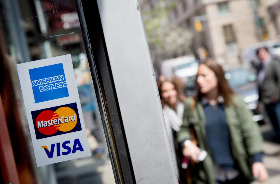 The American Express Co. logo, along with those of Visa Inc. and Mastercard Inc., are displayed in a shop window in New York, U.S., on Monday, April 15, 2013. American Express Co., the biggest U.S. credit-card issuer by purchases, named Edward P. Gilligan to become its president, effective immediately.